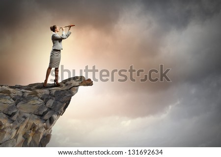 Image of businesswoman looking in telescope standing atop of rock - stock photo