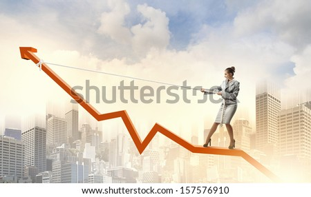 Image of businesswoman standing on graph. Income and profit