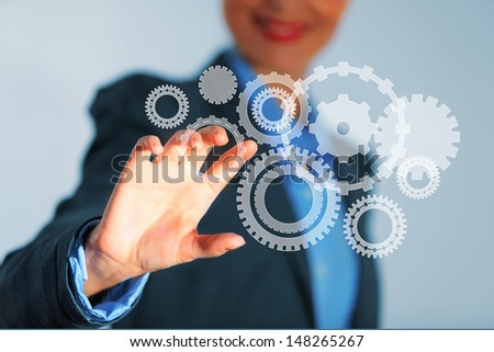 Image of businesswoman touching gear elements. Mechanism concept