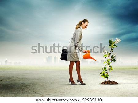 Image of businesswoman watering money tree with pot - stock photo