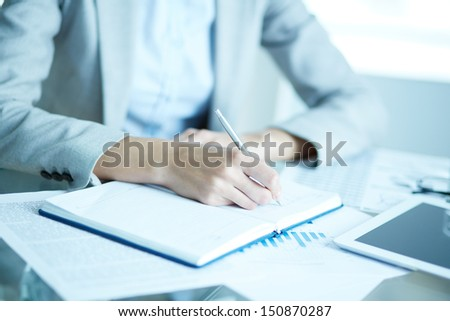 Image of businesswoman writing in notepad at workplace