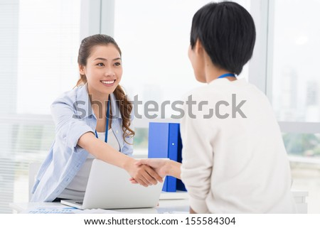 Image of businesswomen handshaking in the sign of agreement - stock photo