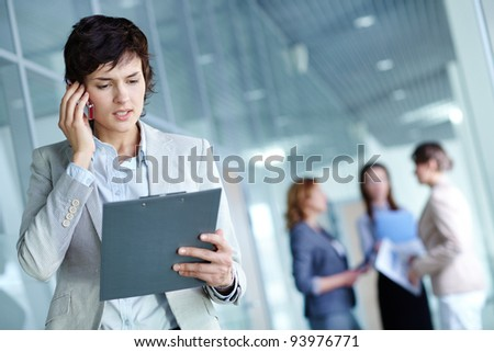 Image of busy female calling on the phone and reading document in working environment - stock photo