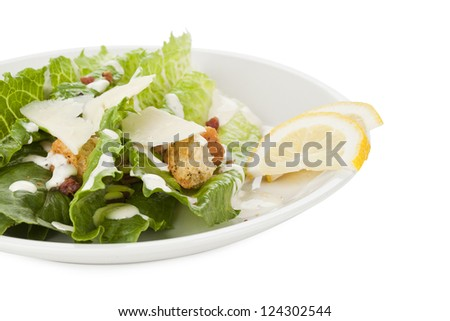 Image of Caesar salad in white plate with lemon slices against white background - stock photo
