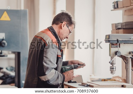 Image of carpenter using electric drill. The carpenter uses a drill in the production workshop of carpentry