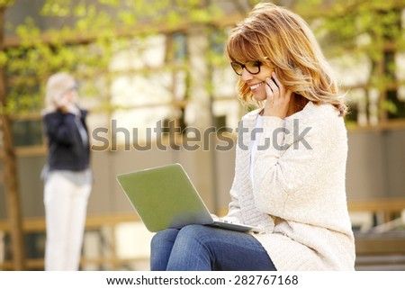 Image of casual businesswoman sitting at outdoor while using her laptop and making call with mobile. Business people at work.  - stock photo