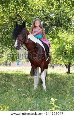 Image of caucasian little girl with long healthy hair sits astride a ponies and smiling in a summer park