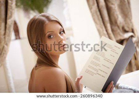 Image of charming young lady reads menu - stock photo