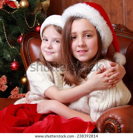 Image of cheerful little girls sitting in vintage arm chair on Christmas time on Holiday theme