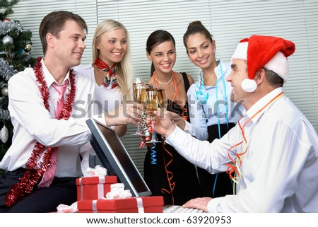 Image of cheering associates making toast with ceo in Santa cap at corporate party - stock photo