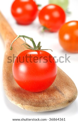 Image of cherry tomatoes with spoon placed on a white background