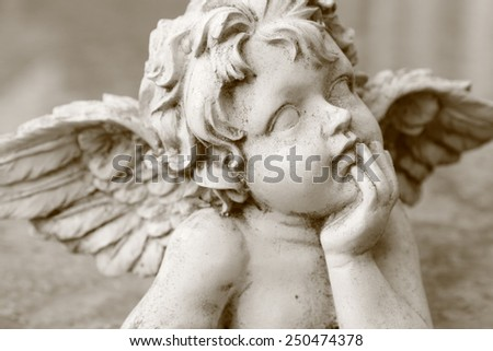 image  of cherub figurine in sepia - stock photo