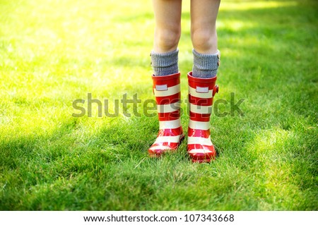 Image of child legs on a green lawn wearing red striped rain boots - stock photo