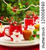 Image of Christmas table decoration, luxury festive utensil over green fir tree background, little red berry twig and star toy decorated table setting in New Year eve, x-mas holiday banquet - stock photo