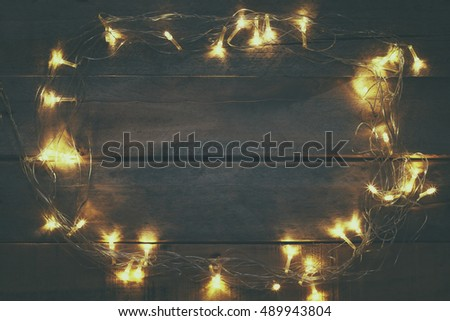 image of Christmas warm gold garland lights on wooden rustic background. filtered image. selective focus.