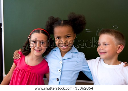 Image of clever classmates standing by blackboard and smiling at camera
