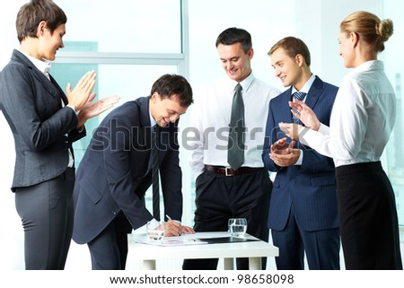 Image of co-workers congratulating their colleague while he signing paper at meeting - stock photo