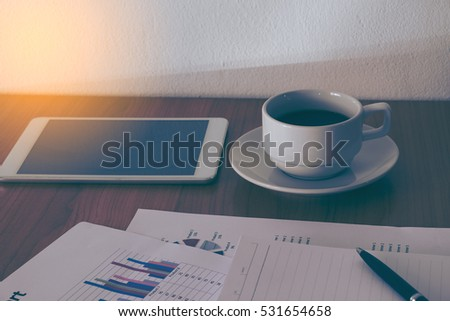Image of coffee on desk of working businesspeople at meeting