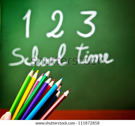 """Image of colorful pencils and green chalkboard with selective focus, multi colors crayons in preschool, handwriting phrase """"school time"""" on blackboard in classroom, education and knowledge concept - stock photo"""