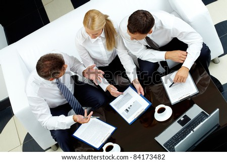 Image of company of successful partners discussing business plan at meeting - stock photo