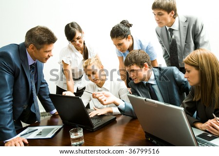 Image of company of successful partners looking at laptop monitor while successful man pointing at it