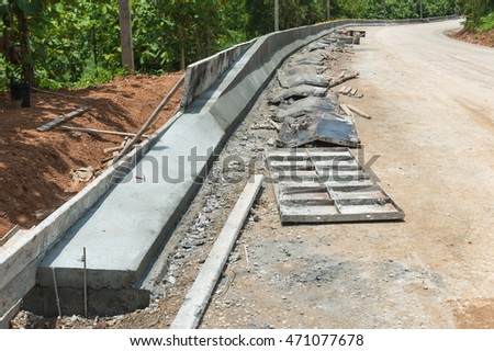 Image of Concrete construction sidewalk, curb and storm drainage gutter on a new urban road street project in Thailand. Selective focus and shallow dof.