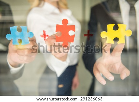 Image of confident business people wanting to put pieces of puzzle together. Close-up.