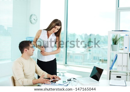 Image of confident businessman with tablet looking at pretty colleague near by - stock photo