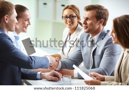 Image of confident businessmen handshaking at meeting