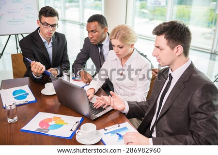 Image of confident colleagues communicating with their boss at meeting.