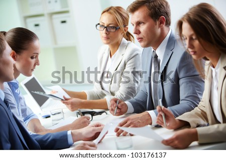 Image of confident man explaining something to his colleague at meeting