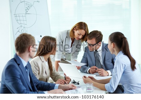 Image of confident partners discussing paper at meeting - stock photo