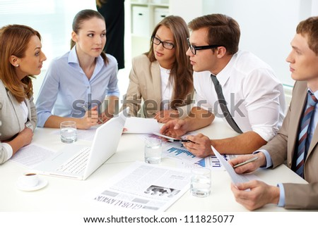 Image of confident partners looking at their colleague at meeting