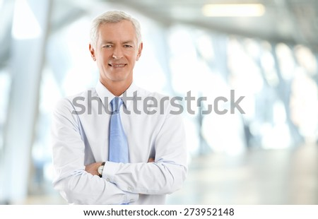 Image of confident senior businessman standing at office with arms crossed and looking at camera. - stock photo