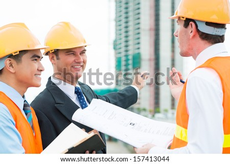 Image of constructor engineers busy with work on the foreground - stock photo