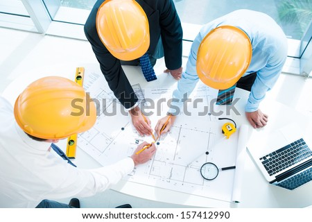 Image of constructor workers sketching together on the foreground viewed below - stock photo