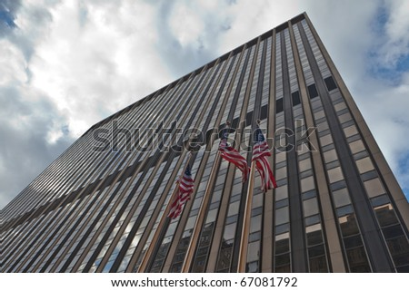 Image of corporate America: Skyscraper with American flags waving in New York city. - stock photo