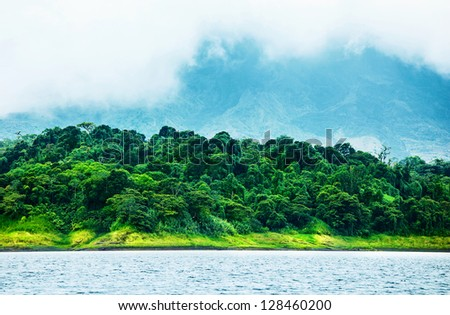 Image of Costa Rica, nature of Central America, fog in the mountains, green forest near river, beautiful landscape, eco tourism, panoramic scene, peaceful nature, travel and vacation concept - stock photo