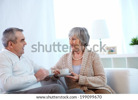 Image of couple of pensioners drinking tea and talking at home - stock photo