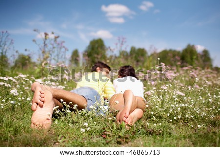 Image of couple resting with their legs in foreground - stock photo