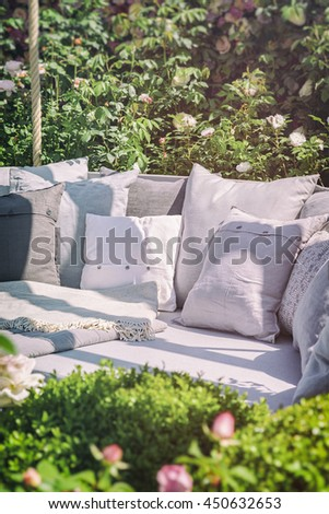 Image of cozy garden seating area with cushions. Vintage filtered.