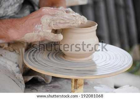 image of craftsman making vase from fresh wet clay on pottery wheel, closeup on hands - stock photo