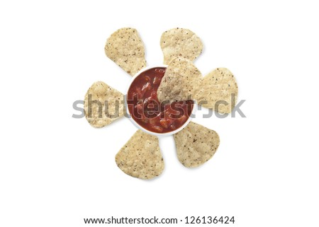 Image of crunchy nachos dipped into a bowl with salsa against the white background - stock photo