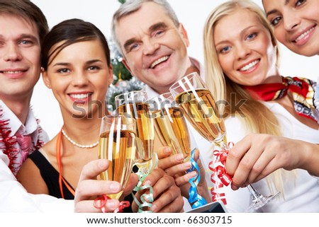 Image of crystal glasses full of champagne held by successful companions