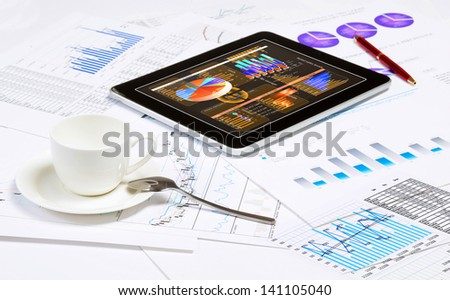 Image of cup of coffee and ipad laying on business documents - stock photo