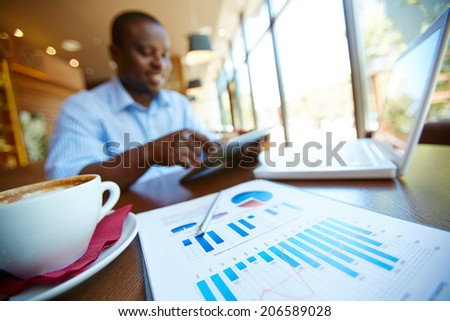 Image of cup of latte and business document on background of man using touchpad in cafe - stock photo