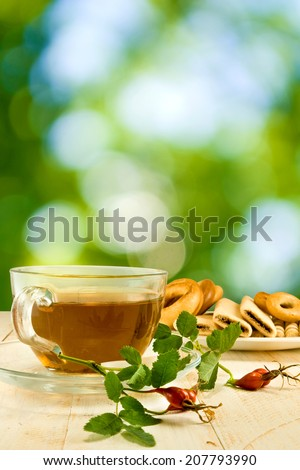 image of cup of tea, cookies and briar branch on a green background