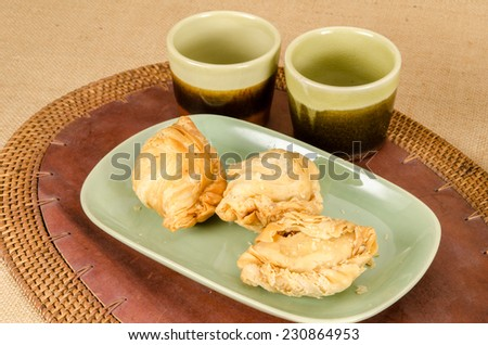 Image of curry puff in green ceramic dish on brown sack background
