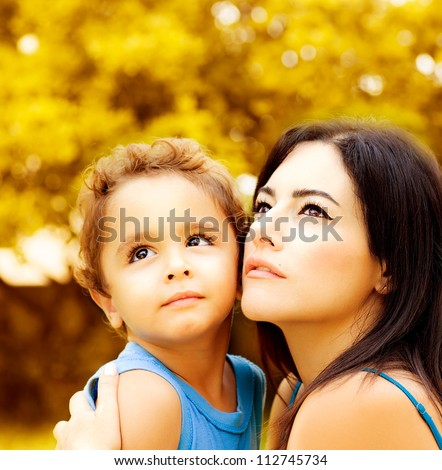 Image of cute baby boy hug his lovely mom in autumn park, closeup portrait of young arabic woman with son looking up on golden autumn background, happy family and love concept - stock photo
