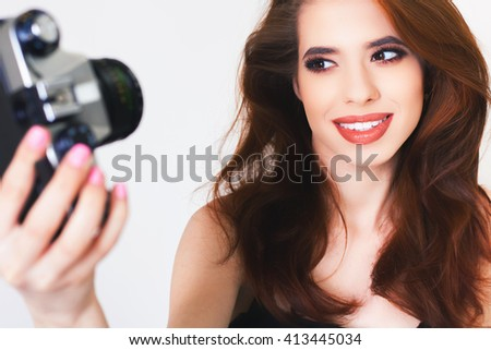 Image of cute girl make a photo selfi at vintage camera. Take a photograph of herself. Funny, party. Beauty. Happy girl smiling. Makeup and hairstyle - stock photo